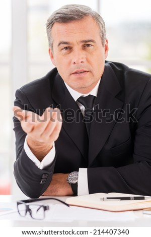 Tell me about yourself! Confident mature man in formalwear looking at camera and gesturing while sitting at his working place - stock photo