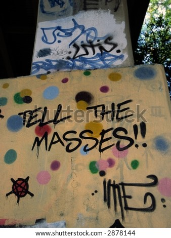 Tell the Masses! Graffiti on bridge pylon - stock photo