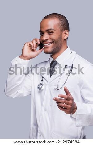 Telling good news. Happy African doctor talking on the mobile phone and smiling while standing against grey background - stock photo