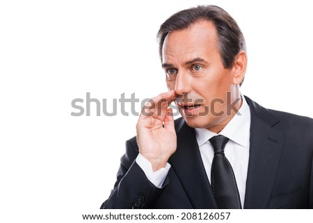 Telling gossips. Portrait of mature businessman telling gossips while holding hand near mouth and standing isolated on white background