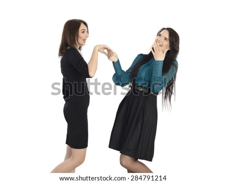 Telling shocking news. Young woman shocked with news told by her friend holding hands of each other and expressing shock on her face formal dress code on white background - stock photo