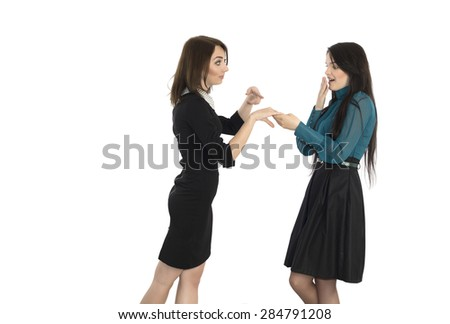 Telling shocking news. Young woman tells to her friend the news about her engagement pointing on finger with wedding ring formal style dress code on white background - stock photo