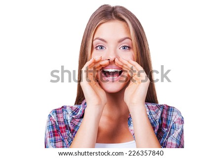 Telling the great news. Attractive young woman shouting and holding hand near mouth while standing isolated on white