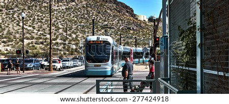 Tempe, Arizona, USA, March 7, 2015 Mill Avenue Metro train, People waiting for train to pass through intersection - stock photo