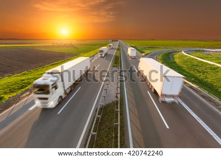 Temperature controlled trucks driving towards the sun. Fast blurred motion drive on the freeway at beautiful sunset. Freight scene on the motorway near Belgrade, Serbia. - stock photo