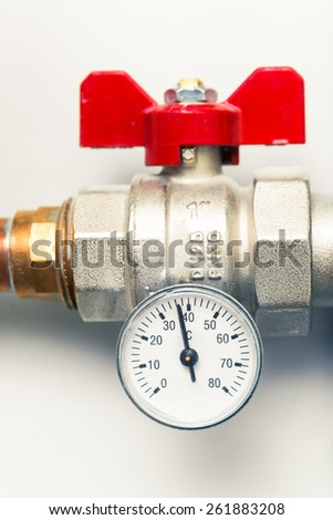 temperature gauge with water tap in boiler-room - stock photo