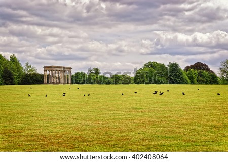 Temple of Concord and black rooks in Park of Audley End House in Essex in England. It is a medieval county house. Now it is under protection of the English Heritage. - stock photo