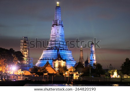 Temple of Dawn, Wat Arun is a Hindu pagoda Khmer architecture temple along the Chao Phraya river, illuminated in blue at night, Bangkok, Thailand - stock photo