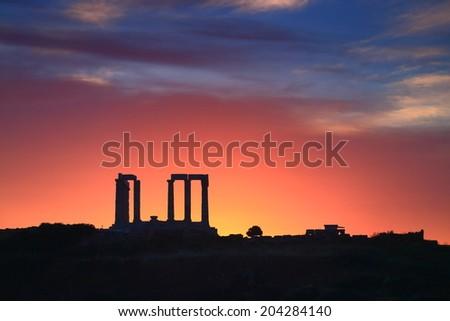 Temple of Poseidon against reddish sky at sunset, Cape Sounio, Greece - stock photo