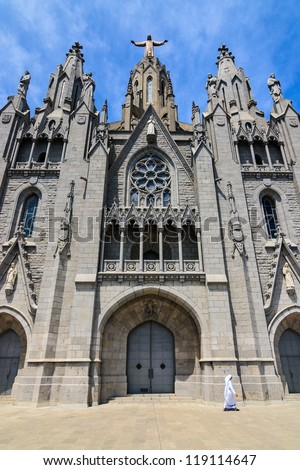 Temple of the Sacred Heart in Barcelona with a nun walking on the court