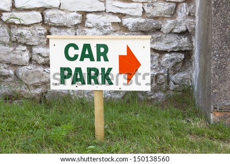 Temporary car park sign  with red arrow direction indicator on wooden post stuck in the ground - stock photo