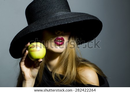 Tempting blonde girl in retro black hat with bright make up holding fresh green apple standing on gray background copyspace, horizontal picture - stock photo