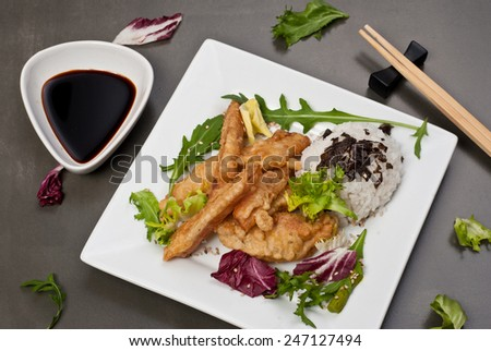 Tempura chicken (deep fried chicken) on white plate on gray table - stock photo