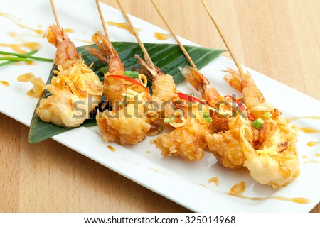 Tempura jumbo shrimp skewers on a white plate. - stock photo
