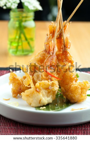 Tempura jumbo shrimp skewers on a white plate standing up vertically. - stock photo