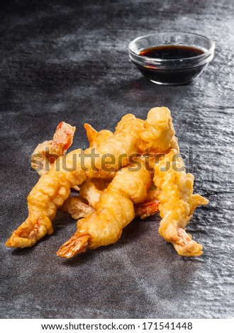 Tempura shrimps with pepper and soy sauce on stone texture - stock photo