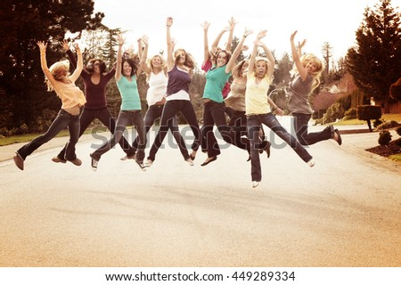 Ten beautiful girls, outside jumping for joy.  - stock photo
