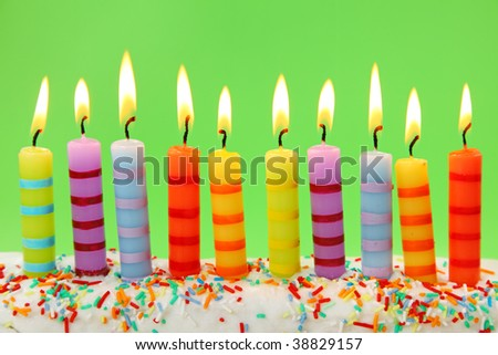 Ten birthday candles on green background