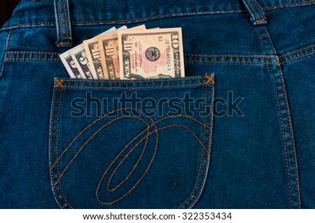 Ten dollar banknotes in denim jeans pocket - stock photo