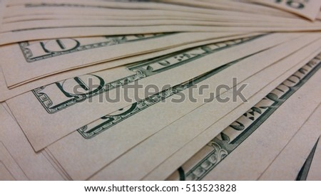 ten dollar bills fanned out on a table are a close-up blur
