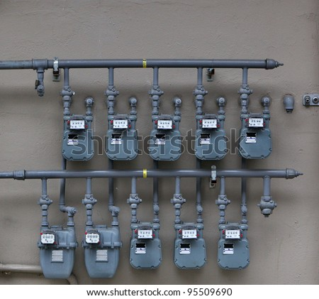 Ten Gray Gas Meters on the wall of an apartment building - stock photo
