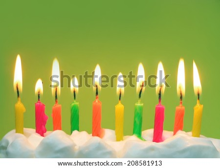 Ten lit brightly colored candles in soft white icing with bright green background. Horizontal composition with copy space in upper part of image. Good for birthdays, anniversaries and milestones