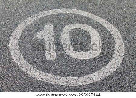 Ten Miles per hour painted road sign on asphalt - stock photo