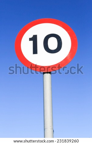 Ten miles per hour speed limit sign against a clear blue sky. - stock photo