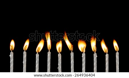 Ten silver burning candles on black background - stock photo