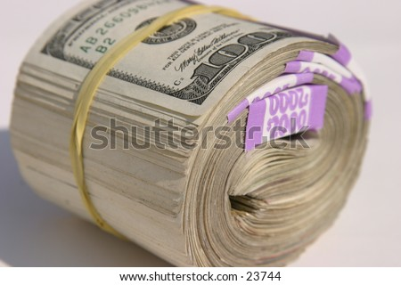 Ten Thousand Dollars American Cash rolled up and held together with yellow rubber band, as if laying on the ground for YOU the viewer! - stock photo
