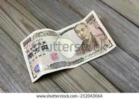 ten thousand yen banknotes on wooden background - stock photo