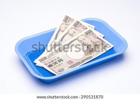Ten thousand yen bills in payment tray - stock photo
