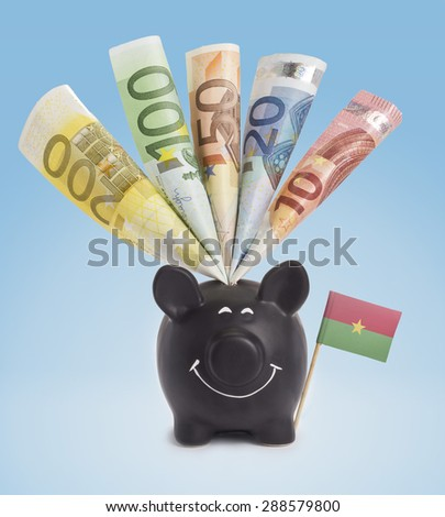 Ten,twenty,fifty,one hundred and a 200 Euro banknote in a smiling piggybank of Burkina Faso.(series) - stock photo