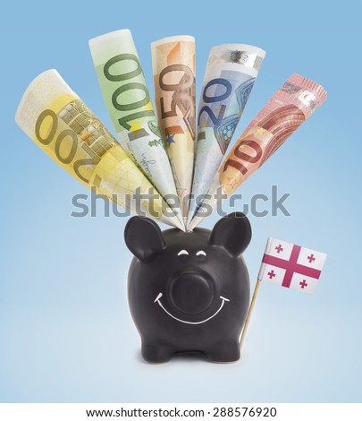 Ten,twenty,fifty,one hundred and a 200 Euro banknote in a smiling piggybank of Georgia.(series) - stock photo