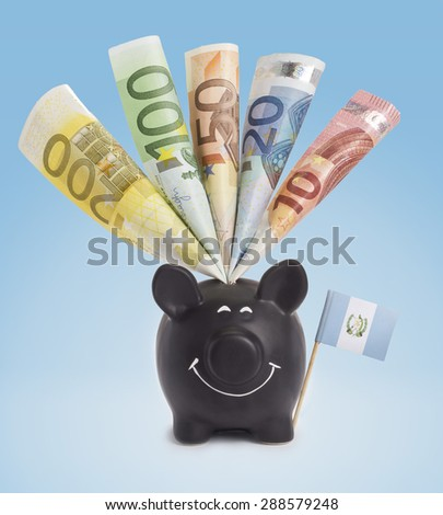 Ten,twenty,fifty,one hundred and a 200 Euro banknote in a smiling piggybank of Guatemala.(series) - stock photo