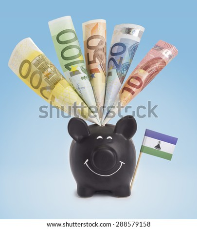 Ten,twenty,fifty,one hundred and a 200 Euro banknote in a smiling piggybank of Lesotho.(series) - stock photo