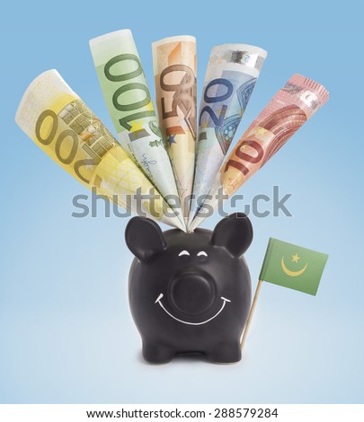 Ten,twenty,fifty,one hundred and a 200 Euro banknote in a smiling piggybank of Mauritania.(series) - stock photo