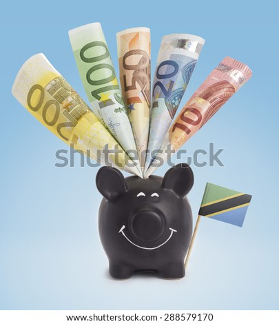 Ten,twenty,fifty,one hundred and a 200 Euro banknote in a smiling piggybank of Tanzania.(series) - stock photo