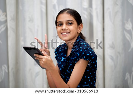 ten year girl playing with her tablet pc or tab in her house sitting on a sofa or a wooden chair against white curtain and showing a sign of victory - stock photo