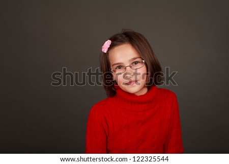 Ten year old dark haired girl with glasses in a bright red sweater - stock photo