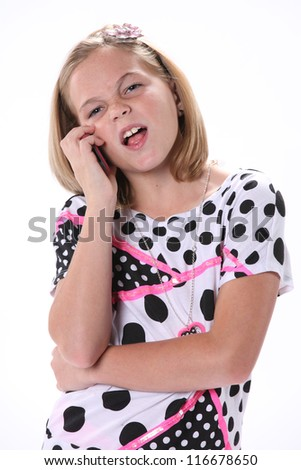 Ten year old female girl in pink standing talking on phone isolated against a white background with copy space in the vertical format. - stock photo