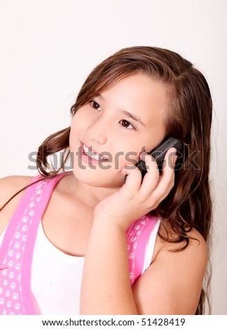 Ten year old girl talking on the phone with pink dress - stock photo