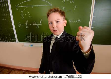 Ten years boy shakes his fist at someone at a classroom.