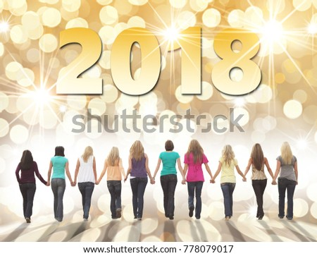Ten young women walking hand in hand on a festive holiday background. Happy New Year 2018