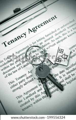Tenancy agreement and key with symbolic house keyring - stock photo