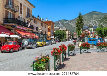 TENDE, FRANCE - AUGUST 12, 2014: Restaurants and bars along narrow road through Tende - small tourist town in French Alps, located on old route of salt trade and known for its cheese, honey and jams. - stock photo