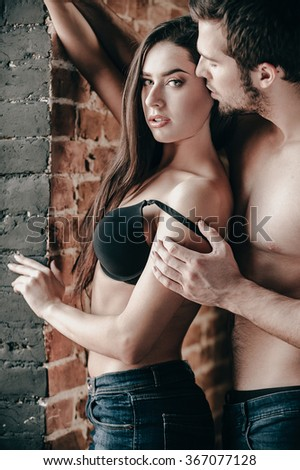 Tender and sensual. Handsome young shirtless man pulling down bra strap of his beautiful girlfriend while both standing near the brick wall