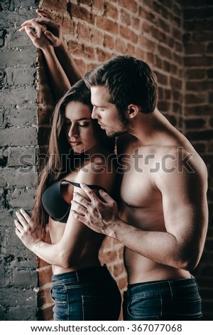 Tender and sensual. Side view of beautiful young shirtless couple in jeans bonding to each other while man taking off bra from his girlfriend  - stock photo