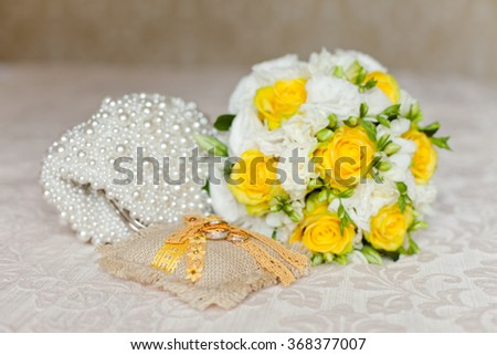 Tender Bride's bouquet in yellow and white colors and wedding rings on a pillow