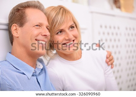 Tender feelings. Agreeable vivacious delighted adult couple smiling and looking up while bonding to each other - stock photo